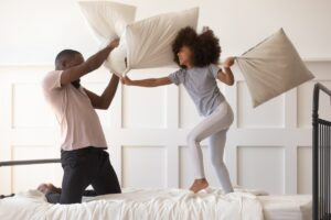 Dad and child in new bedroom playing with pillows